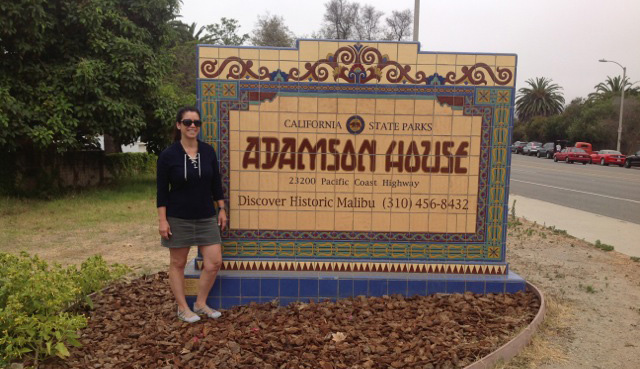 Judy standing aside the handmade tiled Adamson House entry sign