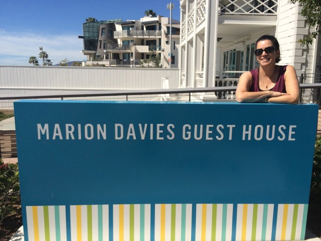 Judy standing behind the Marion Davies Guest House sign.